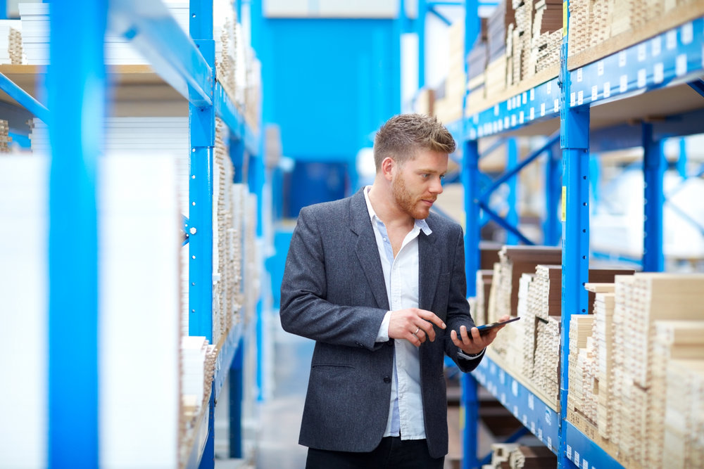 Young businessman in warehouse checking goods on racks