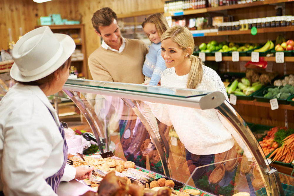Female Sales Assistant Serving White British Family In Delicatessen