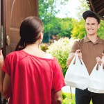 Young delivery man delivering chinese take away food for young woman, standing at the entrance door and holding two plactic bags in hands.