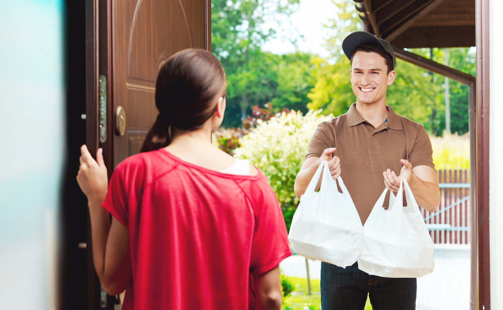 Young delivery man delivering chinese take away food for young woman standing at the entrance