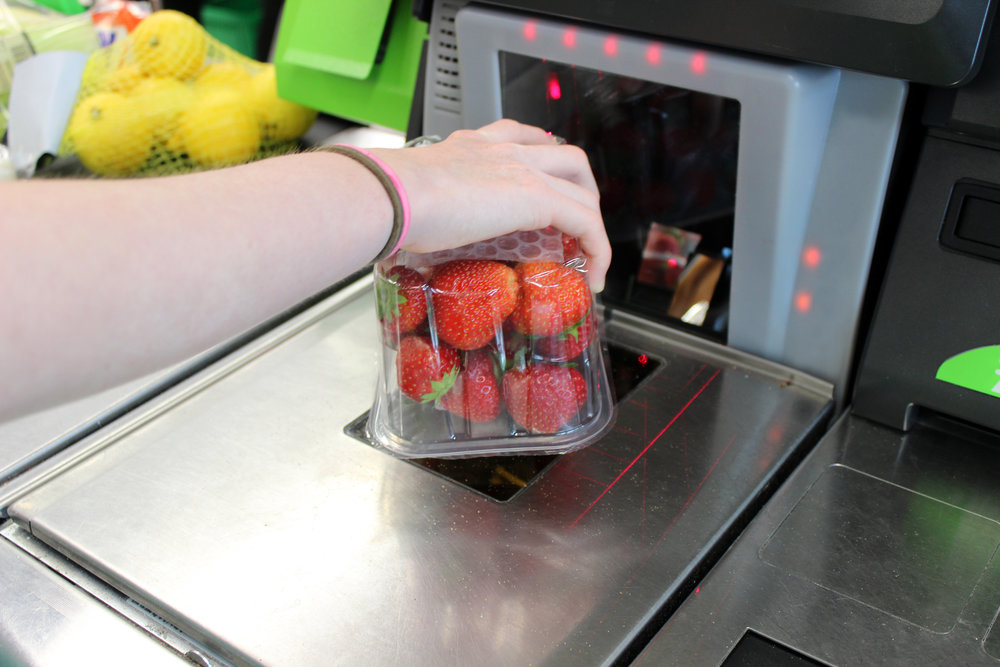 Photo showing a girl scanning her shopping (including fresh fruit / organic strawberries) at a self-service supermarket checkout till (also known as 'Self Checkouts' and 'Semi Attended Customer Activated Terminals' - SACAT. Self-service checkouts are quickly becoming commonplace in large supermarkets, reducing staff costs and replacing the need for cashiers.