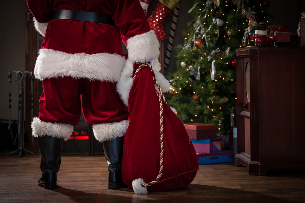 Real authentic Christmas photo of Santa Claus from behind and waist down, holding his bag and standing in a living room in front of the fireplace.