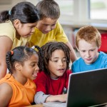 A multi-ethnic group of elementary age children are sitting in class playing an educational game on a laptop.