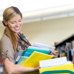 Mid adult Caucasian woman is librarian in elmentary school library. She is smiling while putting books away on bookshelves. She is pushing a rolling cart filled with children's books, and is wearing casual trendy clothing.