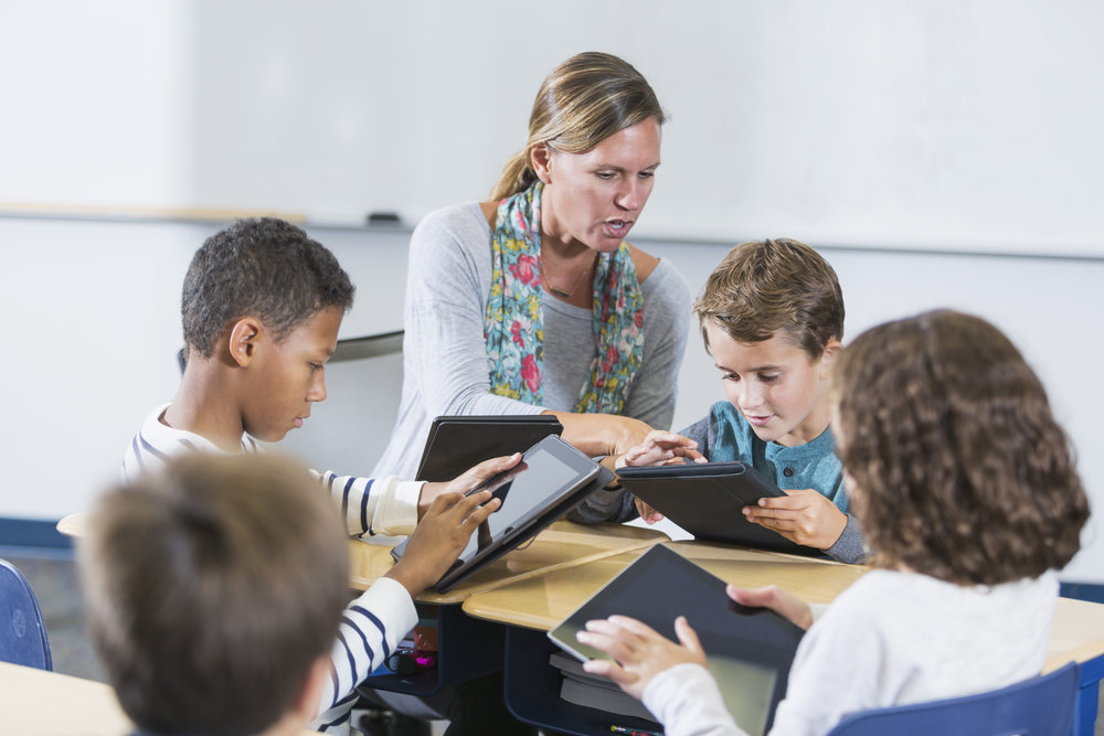 A teacher and a multi-ethnic group of elementary school children sitting around a table in the classroom, each one using a digital tablet. The woman is helping a boy use his.