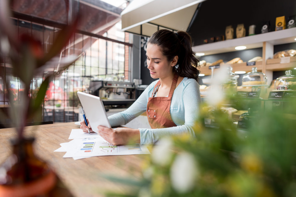 Happy Latin American business woman doing the books at a restaurant