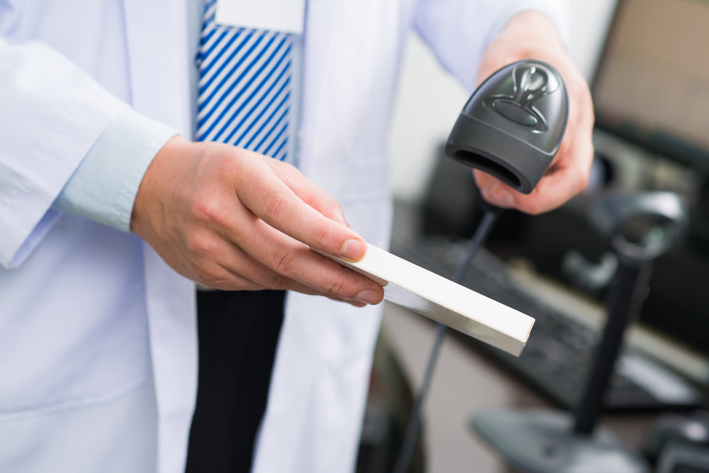 Cropped image of a pharmacist scanning bar code on the foreground