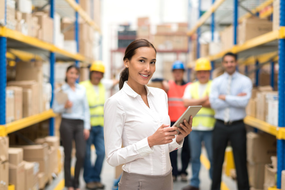 Asian business woman working at a warehouse as a manager with a group of workers at the background