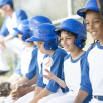 A multi-ethnic group of elementary age boys are sitting in the bench waiting for their turn to bat during the baseball game.