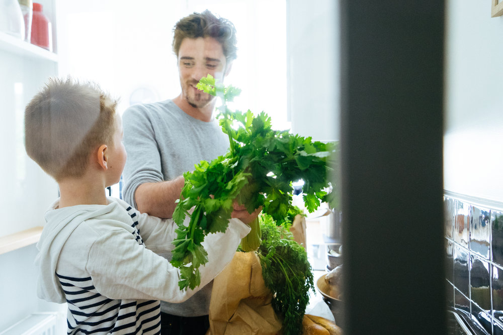 Happy father and son organizing groceries in the kitchen, paper bags full of healthy fresh food.
