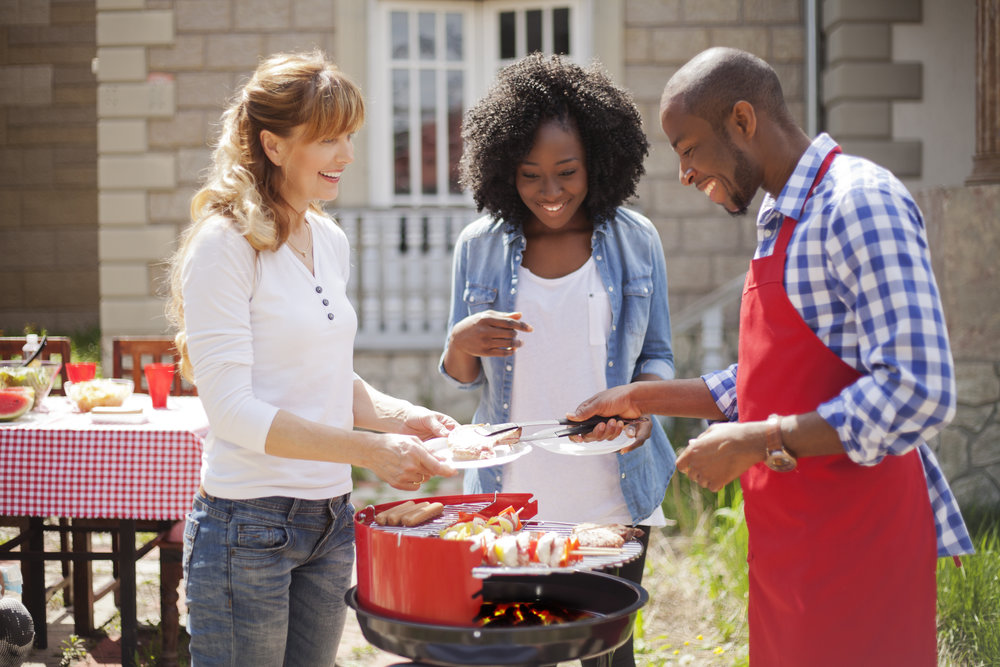 Smiling african decent couple with their caucasian friend make barbecue at their back yard. Little african decent girl is in background