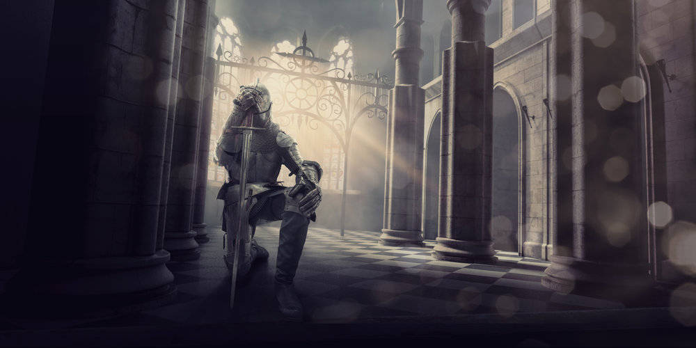 A medieval knight in full suit of armour kneels whilst holding his sword to his head in contemplation or prayer before a big battle. The knight is inside an ancient medieval stone building, which could be a castle or cathedral as the evening from the setting sun streams through the windows.